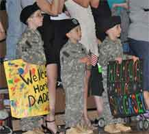 Photo by Geoffrey Roper.  Three young boys dressed as Soldiers await the real Soldiers of 4th Brigade Combat Team, 4th Infantry Division, before the start of the welcome home ceremony held at the Special Events Center Sunday. More than 1,000 Soldiers returned to the Mountain Post during the past week.