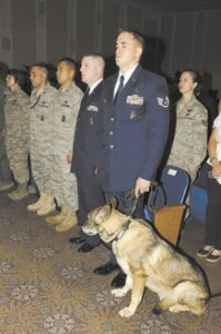 Staff Sgt. Nicholas Pospischil, 21st Security Forces Squadron, and military working dog Wodan, during Wodan's retirement ceremony June 8 at Peterson AFB. Wodan was a patrol and explosive detector who served seven years in the U.S. Air Force, providing protection and support for both handlers and the installation. (U.S. Air Force photo/Roberta McDonald)