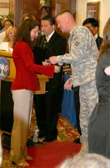 Maj. Gen. David G. Perkins, commanding general, 4th Infantry Division and Fort Carson, congratulates Katherine Boivin, Army Community Service and Cub Scouts volunteer, for her receipt of the Columbine Award of Excellence at an awards ceremony held for Fort Carson volunteers May 18 at the Elkhorn Conference Center.