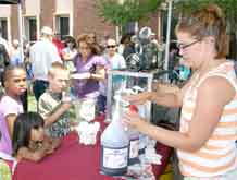 Community members line up for free snow cones at the Army Community Service 45th birthday celebration July 29.