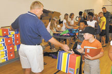 """Rusty Moomey, the principal of Mitchell High School in Colorado Springs School District No. 11, hands a school """"Tool Box"""" to Samuel Brayman, son of Lt. Col. Crismon Brayman. Mr. Moomey volunteered at the 21st Force Support Squadron's """"Back to School Bash"""" held at the R.P. Lee Youth Center gym on Aug. 3. The bash was held in conjunction with National Night Out and included games, arts and crafts and free school supplies. (U.S. Air Force photo/ Rob Bussard)"""