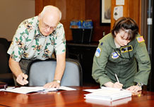 Marc Drake, representative of Boeing Corp, and Lt. Col. Jennifer Grant, 2nd Space Operations Squadron commander, sign the official transfer documents during the official acceptance of the GPS IIF Satellite in the wing conference room Aug. 25. The historic event marked the transfer of the first GPS IIF system from Global Positioning Systems Wing. (Air Force Photo/Dennis Rogers)