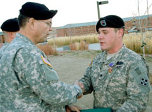 Brig. Gen. James H. Doty Jr., acting senior commander, 4th Infantry Division and Fort Carson, shakes hands with Purple Heart recipient Spc. Joshua Cressey Nov. 22, outside the 1st Brigade Combat Team, 4th Inf. Div. headquarters building at Fort Carson. Cressey an infantryman with Company C, 1st Battalion, 66th Armor Regiment, 1st BCT, 4th Inf. Div., received the medal for battlefield injuries in August, while patrolling Arghandab River Valley, Afghanistan.