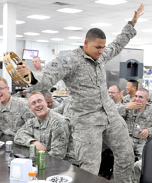 Pfc. Joseph Sylvia, Company A, 1st Battalion, 8th Infantry Regiment, 3rd Advise and Assist Brigade, 4th Infantry Division, bursts into dance with tambourine in hand at the dining facility during a concert performed by the Ivy Division Band rock band, High Altitude, at Contingency Operating Base Garry Owen, Iraq, Dec. 10.
