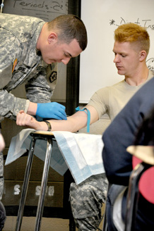 Spc. Blake Anichini demonstrates how to properly give an intravenous infusion on Sgt. Kyle Krull. Soldiers are both with the 52nd Engineer Battalion.