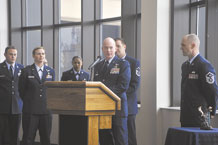 """Lt. Col. Troy Endicott, 21st Operations Support Squadron commander, """"hands over"""" the Intelligence Flight, whose members are to his right, to Col. Nina Armagno, 21st Operations Group commander, during a transition ceremony Jan. 31 on Peterson Air Force Base. Colonel Endicott called it a pivotal ceremony as the intelligence flight moves from the 21 OSS to a new section within the 21 OG called Operations Group Intelligence. He told Colonel Armagno she was inheriting """"the cream of the crop."""" (U.S. Air Force photo/Dennis Howk)"""