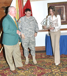 Mike Pfalmer receives the 2010 Good Neighbor award and jacket during the induction ceremony at the Elkhorn Conference Center April 12 from Brig. Gen. James H. Doty, acting senior commander, 4th Infantry Division and Fort Carson, and Ginger Perkins, wife of Maj. Gen. David G. Perkins, commanding general, U.S. Division-North and Fort Carson.