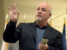 Dave Ramsey holds out a $100 bill during a free financial seminar for servicemembers March 25, inside the Special Events Center. Ramsey waved the cash at a military audience of more than 1,300 people to represent the monthly equity loss caused by car loans.