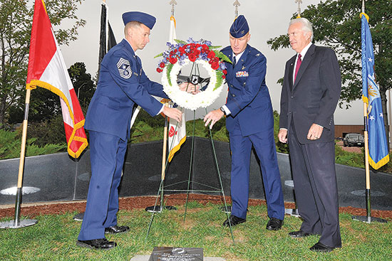 (U.S. Air Force photo/Dennis Howk)  PETERSON AIR FORCE BASE, Colo. — Chief Master Sgt. Richard Redman (left) 21st Space Wing command chief, Col. Michael Hough, 21st SW vice commander, and retired Col. Paul Robinson, place a wreath at the Peterson POW/MIA memorial Sept. 20. Robinson was an Air Force pilot taken as a POW in Vietnam July 1, 1972, and was the guest speaker at the Peterson POW/MIA observance at the base chapel. Robinson was held POW for nine months at the Hanoi Hilton.