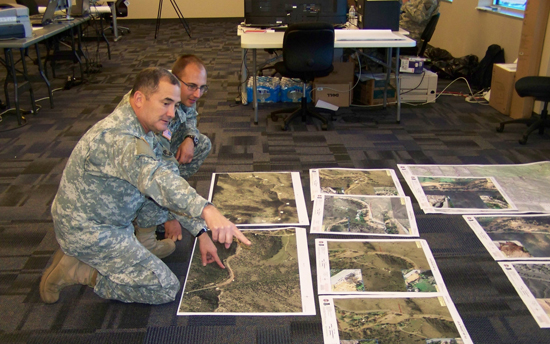 (Colorado Army National Guard photo) Maj. Robert Heslin, Army Space Support Team team leader, 117th Space Battalion, reviews satellite imagery products of Colorado flood damage for the Colorado Department of Transportation with his operations officer, Capt. Chris Meyer.