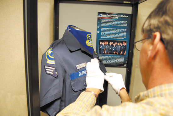 (U.S. Air Force photo/Michael Golembesky) PETERSON AIR FORCE BASE, Colo. — Jeff Nash, 21st Space Wing museum deputy director and curator, puts the finishing touches on a donated uniform that was worn by 1st Space Wing service members during the early '80s. The uniform is currently on display in the waiting area of the military personnel section located in building 350.