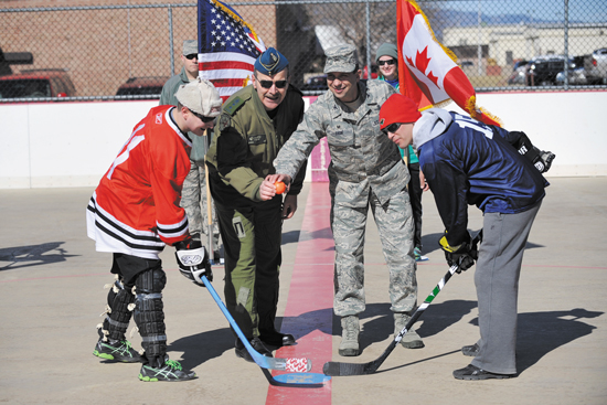 (U.S. Air Force Photo/Robb Lingley) PETERSON AIR FORCE BASE, Colo. — Maj. Gen. Andre Viens of NORAD/NORTHCOM and Col.  John Shaw, 21st Space Wing Commander, drop the ball to start the USA vs Canada Ball Hockey Tournament at Peterson Air Force Base on Feb. 21. The tournament was a best of three series between teams made up of junior Airmen, junior leadership and senior leadership. Team Canada won the first two games and the series with scores of 6-0 in the junior enlisted game and 7-4 in the junior leadership game. Team USA avoided a shutout by defeating Team Canada in the senior leadership game 6-2.