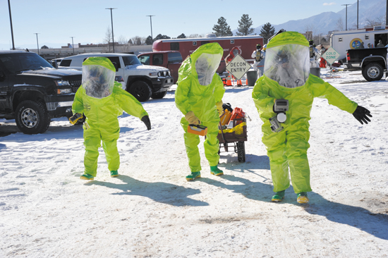 (U.S. Air Force photo/Robb Lingley) PETERSON AIR FORCE BASE, Colo. — Airmen from the 21st Medical Squadron don protective gear before approaching a suspected chemical agent located inside a dumpster during an emergency management exercise here Jan. 28. Condor Crest is designed to test and evaluate installation response to a real-world crisis or base wide situation that requires command and control, first responder employment and cooperation with local law enforcement and community leaders.