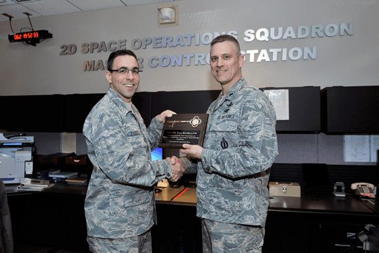 U.S. Air Force photo/Dennis Rogers Col. Bill Liquori, 50th Space Wing commander, accepts the official transfer of the GPS IIF-5 satellite during a ceremony Monday in the 2nd Space Operations Squadron. Lt. Col. Matthew Brandt, 2 SOPS director of operations, receives the official plaque to commemorate the ceremony.