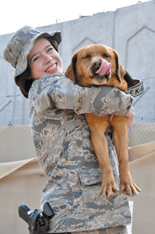 (U.S. Air Force photo/Master Sgt. April Lapetoda) Senior Airman Samantha Baker, a military working dog handler deployed to the 380th Expeditionary Security Forces Squadron, gives her partner, Penny, a hug after successfully completing a training session. Baker is deployed from Peterson AFB.