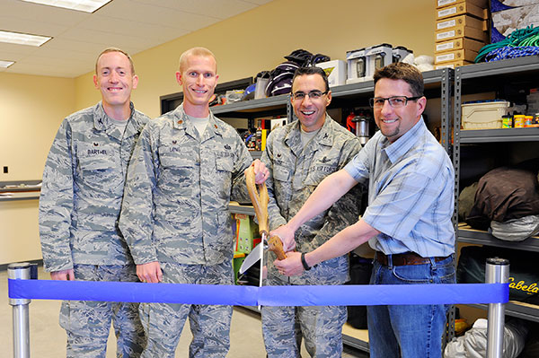 U.S. Air Force photo/Christopher DeWitt Col. Bill Liquori, 50th Space Wing commander (center right), officially opened the remodeled Schriever Outdoor Recreation and Information Travel and Tickets warehouse Friday. Col. Brian Barthel, 50th Space Wing Mission Support Group commander, Maj. Justin Long, 50th Force Support Squadron commander, and Chad McNamee, SB Construction project manager were on hand to help cut the ceremonial ribbon.