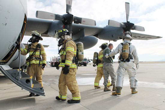 (U.S. Air Force photo/Michael Golembesky)  PETERSON AIR FORCE BASE, Colo. – Service members with the Peterson Air Force Base fire department evacuate the crew of a C-130 Hercules who had declared an in-flight emergency during a return flight from Holloman Air Force Base Nov. 18. Condor Crest is a quarterly exercise designed to test and evaluate base readiness for real-word events.
