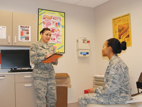 (U.S. Air Force photo by Dave Smith)  Senior Airman Deborah Sosa (left), 21st Medical Operations Squadron medic, discusses events of the day with Capt. Laureal Jones, women's healthcare provider. Sosa called upon her training to assist a pedestrian who was convulsing and laying partially in the street in busy holiday traffic.
