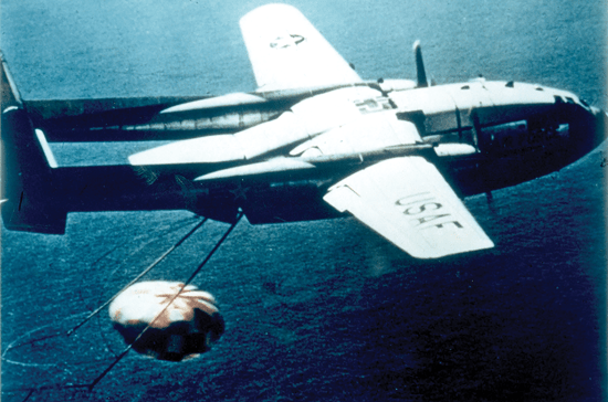 A C-119 aircraft recovers film canister ejected from Discoverer XIV.