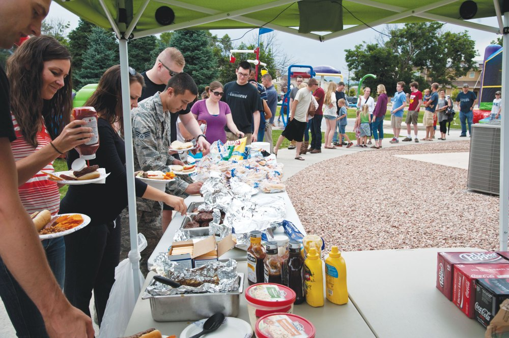 PETERSON AIR FORCE BASE, Colo. – Members of Peterson and their families help themselves to hamburgers and hot dogs during the Peterson Chapel's community cook out at the Tierra Vista community center, July 2, 2015. The Chapel kicked off the July Fourth weekend with approximately 200 people with grilled food, games and music. (U.S. Air Force photo by Senior Airman Tiffany DeNault)