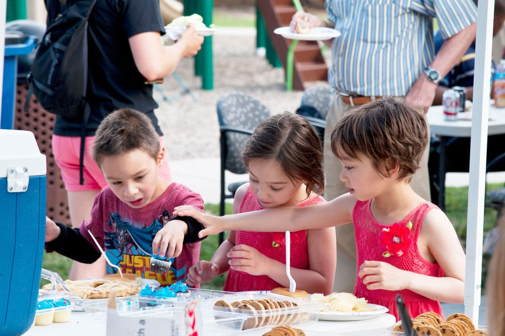 PETERSON AIR FORCE BASE, Colo. – Ethan, Sophia and Amelia Westerberg help themselves to a couple miniature cupcakes during the Peterson Chapel's community cook out at the Terra Vista community center, July 2, 2015. The Chapel provided the grilled food, games and music to approximately 200 Pete members and families. (U.S. Air Force photo by Senior Airman Tiffany DeNault)