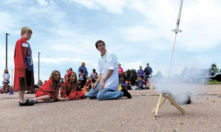 U.S. Air Force photo/Christopher DeWitt Schriever School Age Program students McKinley Cross (left), Kayden Rice and Hannah Withycombe launch the rocket they built, while Monahan LLC Science Camp staff member Sam Birchenough supervises, Thursday, July 2, 2015 at Schriever Air Force Base, Colorado. The rocket launch culminated the SAPs Science Camp week, where, as part of a mock meteorite strike, students also learned about the scientific method to create a theory and hypothesis for the strike, built robots to collect data in a radioactive environment and dissected frogs to check for infections in the environment.