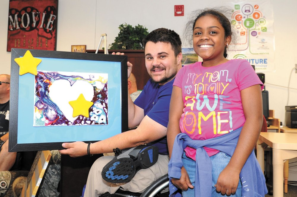 U.S. Air Force photo/Dennis Rogers Retired Staff Sgt. Chris Wolff displays a piece of artwork presented to him by Schriever School Age Program student Ashlyn Richards during a ceremony Friday, Aug. 21, 2015, in the Schriever Child Development Center at Schriever Air Force Base, Colorado. Wolff, a member of the Air Force Wounded Warrior Program, was invited, along with three other members of the program, to the event where they were recognized for their service and sacrifice.