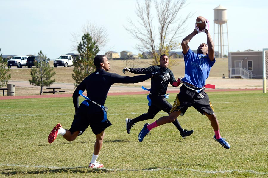 U.S. Air Force photo/Christopher DeWitt Tony Strickland, 4th Space Operations Squadron, makes a leaping catch between two 50th Security Forces Squadron defenders during the intramural flag football championship game at Schriever Air Force Base, Colorado, Thursday, Oct. 15, 2015. Strickland, who took the catch 42 yards for a touchdown, also returned an interception for a touchdown to lead 4 SOPS to a 25-0 victory.