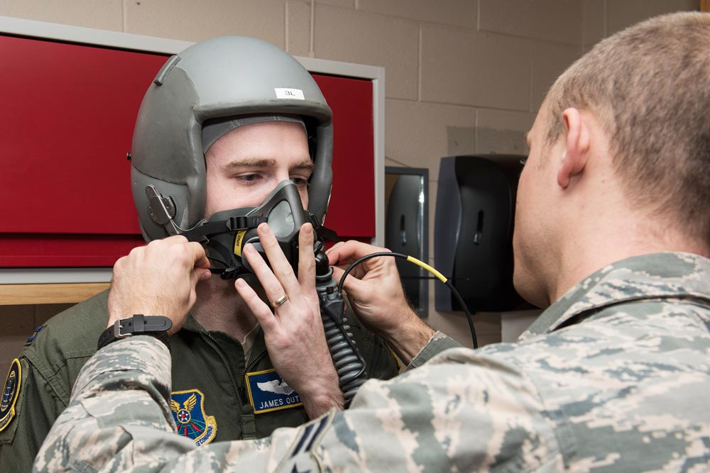 (U.S. Air Force photo by Senior Airman Rose Gudex) PETERSON AIR FORCE BASE, Colo. — Capt. James Outland, 54th Helicopter Squadron from Minot Air Force Base, N.D., gets fitted for a mask before entering the high altitude chamber at the Aerospace and Operational Physiology Lab on Dec. 10, 2015. The high altitude chamber, one of 11 in the Air Force, gives pilots and aircrew members an understanding of how the human body reacts to altitudes and low oxygen.