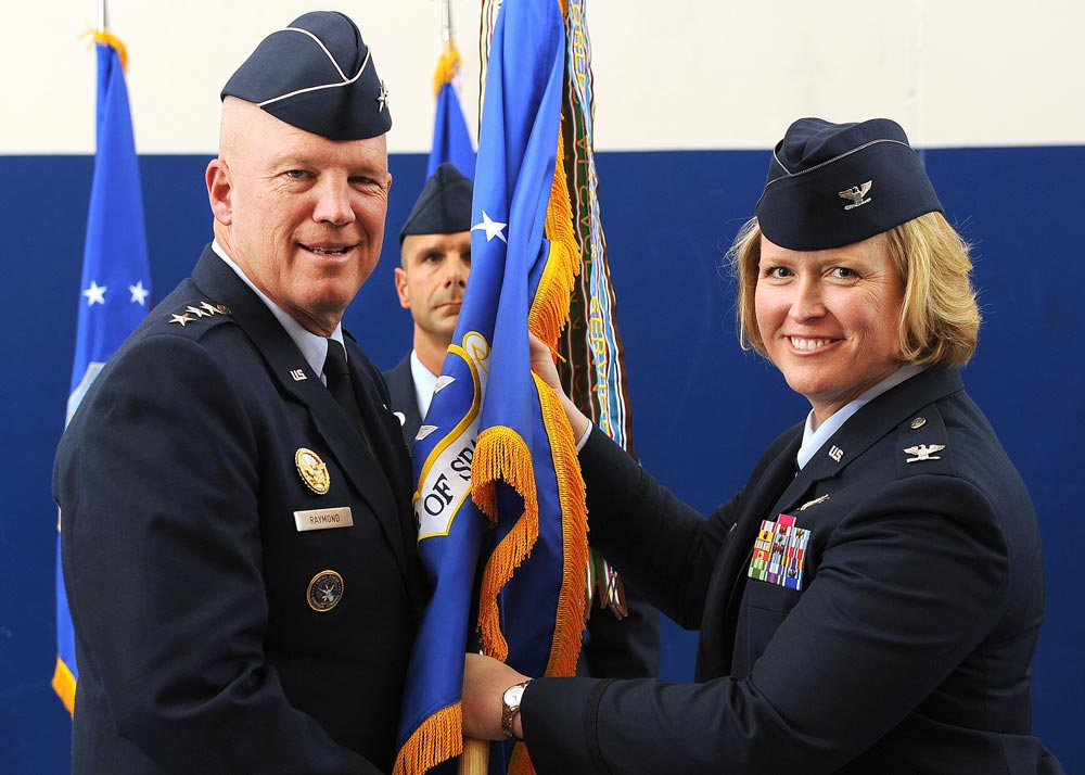 "U.S. Air Force Photo/Dennis Rogers U.S. Air Force Lt. Gen. John W. ""Jay"" Raymond, commander, 14th Air Force (Air Forces Strategic) and Joint Functional Component Command for Space, passes the guidon to Col. DeAnna M. Burt, as she assumes command of the 50th Space Wing, during the change-of-command ceremony in May at Schriever Air Force Base, Colo. As wing commander, Burt is responsible for more than 4,200 military, Department of Defense civilians and contractor personnel serving at 14 operating locations worldwide and operating 69 surveillance, navigation and timing, space situational awareness and communication satellites valued at more than $66 billion."