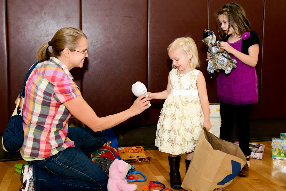 PETERSON AIR FORCE BASE, Colo. – Sarah Lynch and her daughters Liliana and Sophia look through donated toys during the annual clothing swap at the Peterson Youth Center April 23, 2016. Any leftover clothes were donated to the Peterson Thrift Shop and Hope & Home, a Colorado Springs Foster Organization.