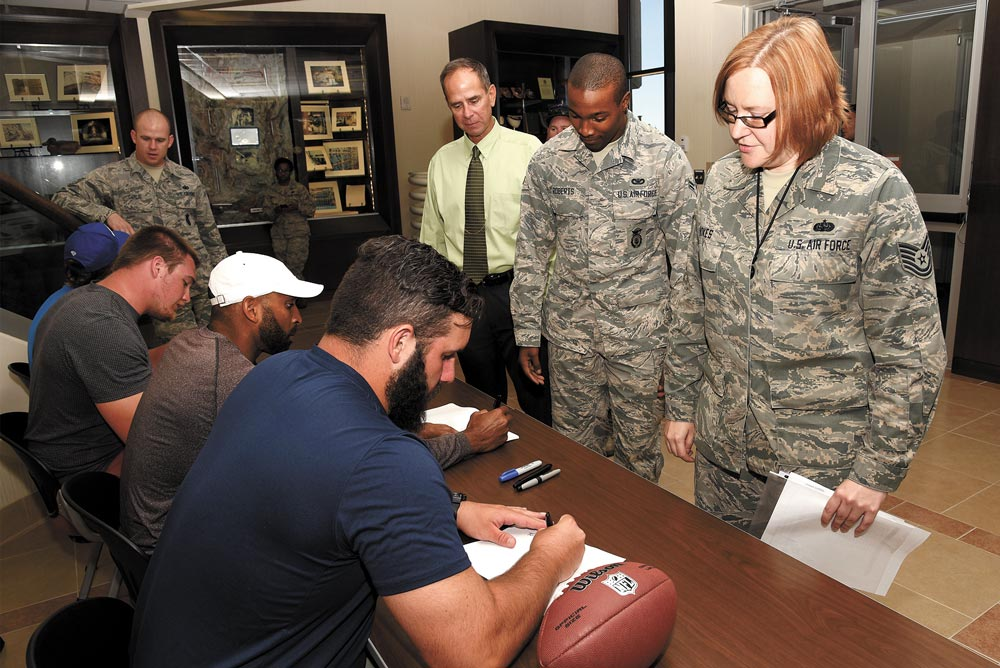 (U.S. Air Force photo by Airman 1st Class Dennis Hoffman) CHEYENNE MOUNTAIN AIR FORCE STATION, Colo. — Players from the NFL meet and sign autographs for Airmen at Cheyenne Mountain Air Force Station, Colo., July 13, 2016. The players were in Colorado Springs for a youth football camp they helped coach.