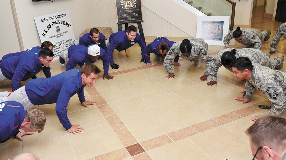 (U.S. Air Force photo by Senior Airman Rose Gudex) CHEYENNE MOUNTAIN AIR FORCE STATION, Colo. — Members of the U.S. Men's Olympic Gymnastics team do 22 pushups with members of the 721st Mission Support Group at Cheyenne Mountain Air Force Station, Colo., July 14, 2016. The gymnasts were at CMAFS to meet Airmen, get a tour of the facilities and learn about its mission.