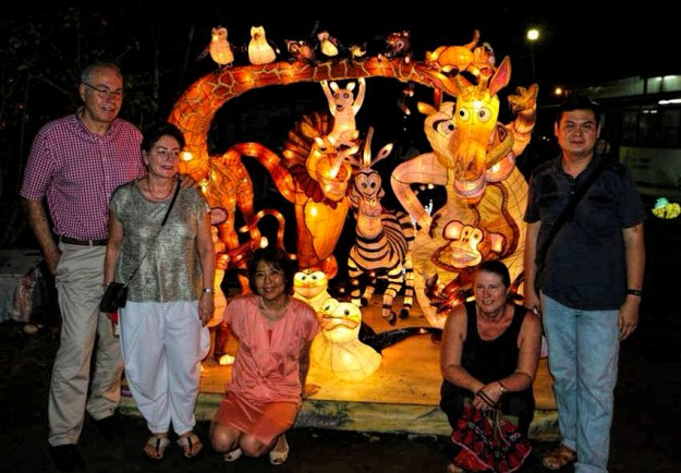 Guests posing in front of the lighted animal structures.