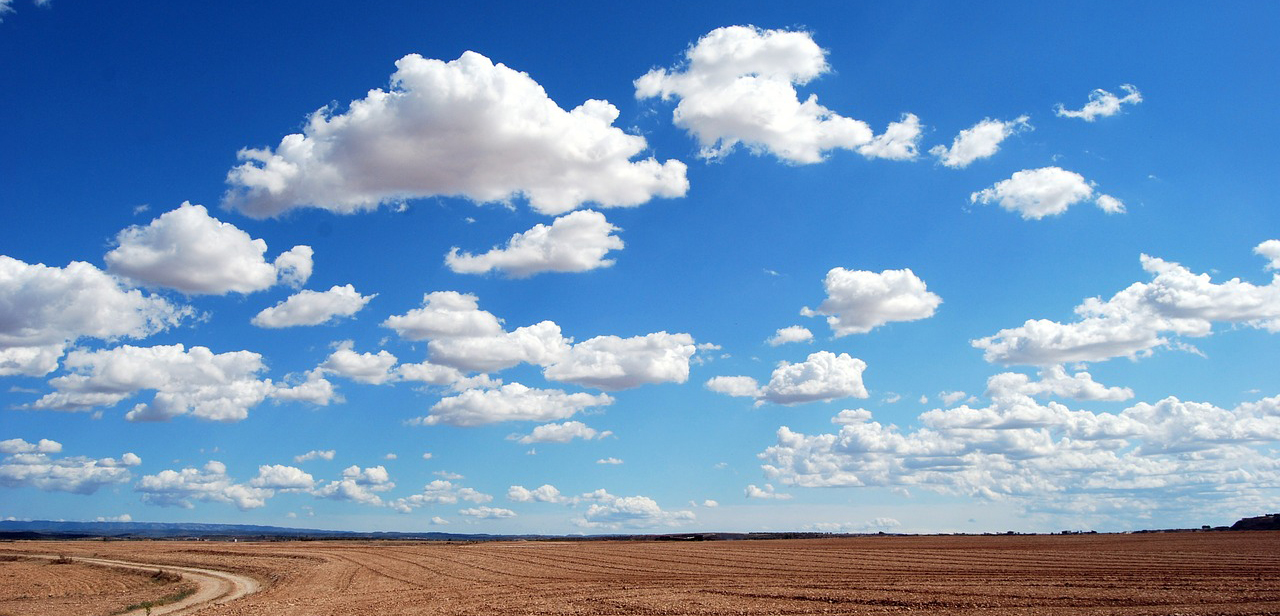 A photo of clouds against a blue sky. The clouds have shades of gray that provide depth.