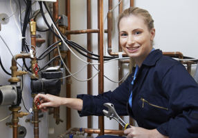 Female Plumber Working On Central Heating Boiler