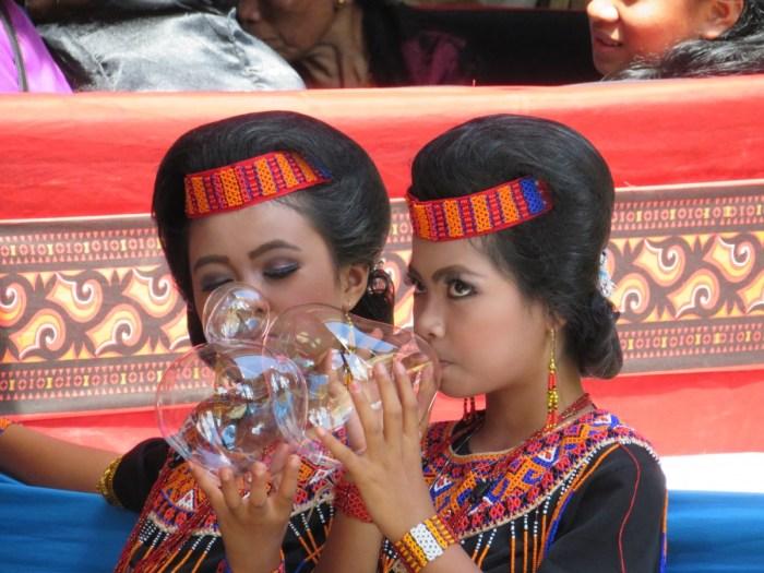 twee jonge meiden in traditionele kleding blazen bellen van suikergoed