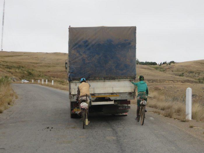 twee fietsers hangen achter vrachtwagen