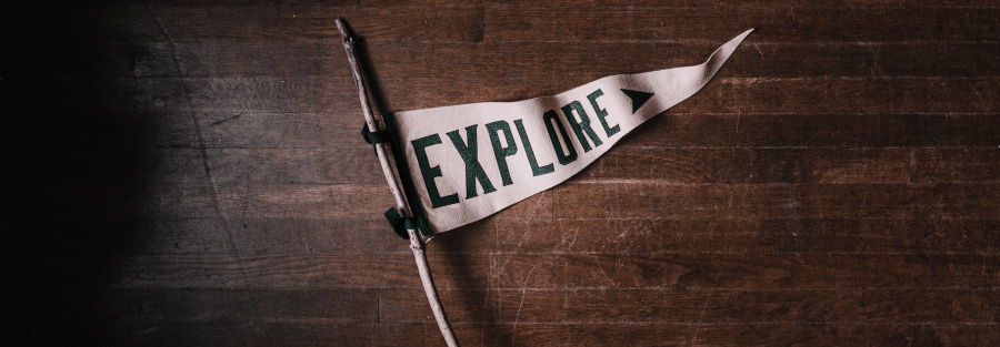 """A flag stating """"Explore"""" attached to a wood stick"""