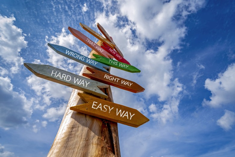 Photograph of a crossroads sign that reads easy way, hard way, right way, wrong way, new way, old way (Credit Take Photo via Shutterstock)