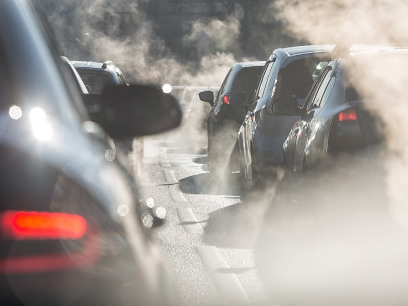 Blurred silhouettes of cars surrounded by steam from the exhaust pipes in a traffic jam. (LanaElcova via Shutterstock)