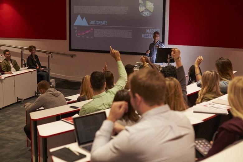 University students raise hands (Monkey Business Images via Shutterstock)