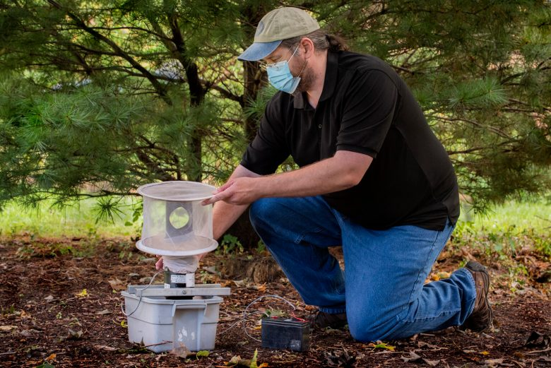 Research assistant Mike Olson of the Connecticut Agricultural Experiment Station demonstrates setting a mosquito trap in the kind of shady area that mosquitoes like.