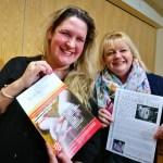 Two females holding leaflets