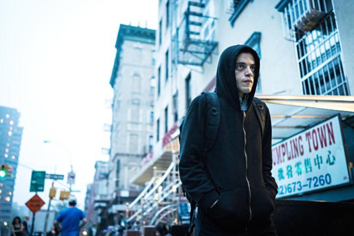 Rami Malek como Hacker antisocial y vestido de negro, con capucha, todo muy topicazo