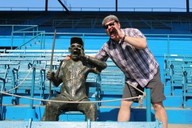 Coach Tom Simon poses with a statue honoring a fan who attended every game for many years at the Estadio Latinoamericano.