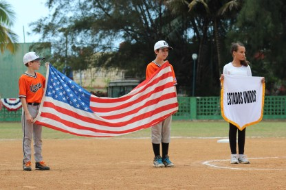 Vermont Player William Gumbrell holds the U.S. flag during the playing of the National Anthem.