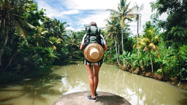 Una joven contempla el paisaje frente a un río tropical (littlehenrabi / Getty Images/iStockphoto)