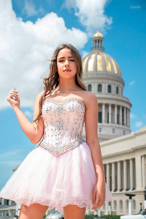 fotografia a quinceañera en vestido rosado frenta la capitilo de cuba en dia soleado