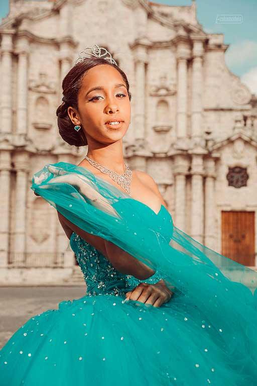foto en primer plano de quinceañera con vestido verde mrino frente a la catedral de la habana vieja en cuba por el estudio de fotografia Cuabmodela